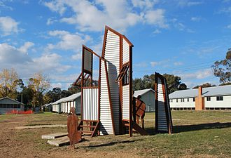 Bonegilla Migrant Reception and Training Centre - A sculpture commemorating the migrants who spent time at the Bonegilla camp. Some of Block 19 can be seen in the background.
