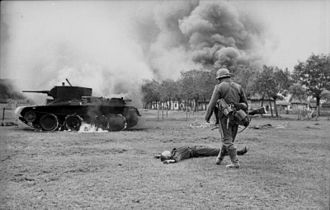 Battle of Brody (1941) - A German infantryman near a burning Soviet BT-5 tank in the distance