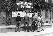 Black and white historical photograph of several men, some with Nazi armbands, reading a newspaper billboard.
