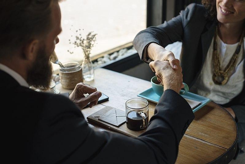 File:Business agreement handshake at coffee shop.jpg
