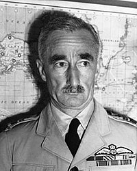 Head-and-shoulders portrait of moustachioed man in light-coloured military uniform with ribbons and pilot's wings on chest