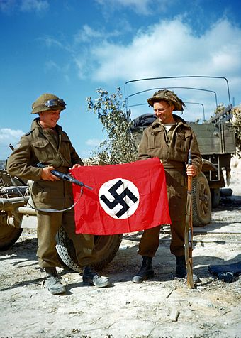 Canadian soldiers with a captured Nazi flag Canadiannaziflag1944.jpg