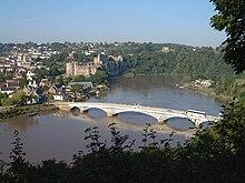 Vue ensoleillée sur un pont métallique blanc en contrebas séparant les deux rives d'un large fleuve. Sur la rive de gauche sont visibles les contours d'une grande ville avec un château médiéval, et sur la rive droite une zone plus rurale