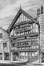 A black-and-white drawing of a three-storey timber-framed building seen from an angle. The lowest storey has a door on the left with a series of windows to the right; glazing extends across the middle storey, with a wide oriel window in the centre; the top gabled storey also contains an oriel window and at the top is an elaborately carved bargeboard.