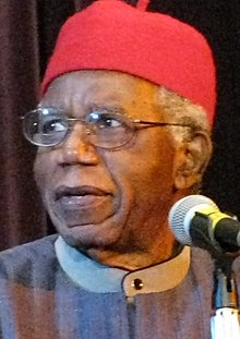 Achebe in blue cap at lectern