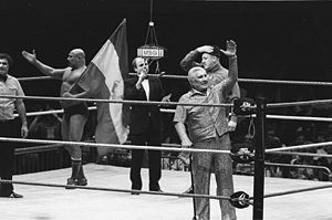 Freddie Blassie - Blassie (right - foreground), with clients The Iron Sheik (left, holding flag) and Nikolai Volkoff (right - directly behind Blassie) during in the mid 1980s at a Madison Square Garden event