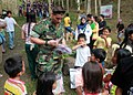 Defense.gov News Photo 100724-A-XXXX-005 - U.S. Navy Petty Officer 3rd Class Timothy Countryman hands out crayons and coloring books to Philippine children during a medical civic action.jpg