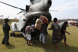 Typhoon Megi (2010) - Victims of Typhoon Megi unload humanitarian aid supplies from a U.S. Marine Corps helicopter in Isabela, Philippines.