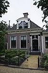 Dorpshuis met door pilasters geflankeerde ingang onder schilddak met grote versierde dakkapel en twee topschoorstenen met borden