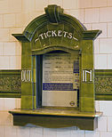 "An elaborate ticket office window, tiled in green terracotta, with the word ""TICKETS"" above the window and ""OUT"" and ""IN"" on the left and right sides"
