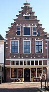 foto van Huis met trapgevel met dekplaten, lijsten, hoekblokken, geblokte ontlastingsbogen en toppilaster op leeuwenmasker