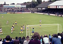 A colour shot of a football match in progress, taken from the terraced stand behind one of the goals. The terraced stand at the far end is without a roof, while the stand to the right is covered