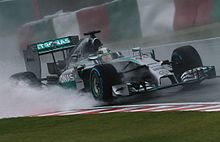 Silver Formula One car in the rain; standing water on the track's surface is lifted by its tyres.