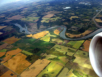 Aspen parkland - The mixture of small patches of trees near rivers and patchworks of farm fields are typical of parkland.  Shown here is the North Saskatchewan River in Alberta circa 2008.
