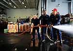 From left, U.S. Navy Machinist's Mate 3rd Class Steven Sanday, Electrician's Mate 2nd Class Brandon Osefoh and Chief Warrant Officer Kevin Davis practice hose-handling techniques during a damage control olympics 130610-N-XE109-160.jpg