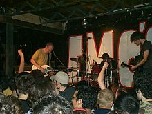 A color photograph of members of the band Fugazi performing on state with the heads of an audience in the foreground