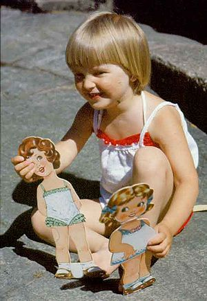 Girl playing with paper dolls.