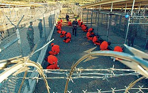 Military prison - Captives at Camp X-Ray a U.S. military prison located in Guantanamo Bay, Cuba, where many people are being indefinitely detained in solitary confinement as part of the War on Terror (January 2002). While awaiting their interrogation, the prisoners are forced to wear goggles and headphones for sensory deprivation and to prevent them from communicating with other prisoners.