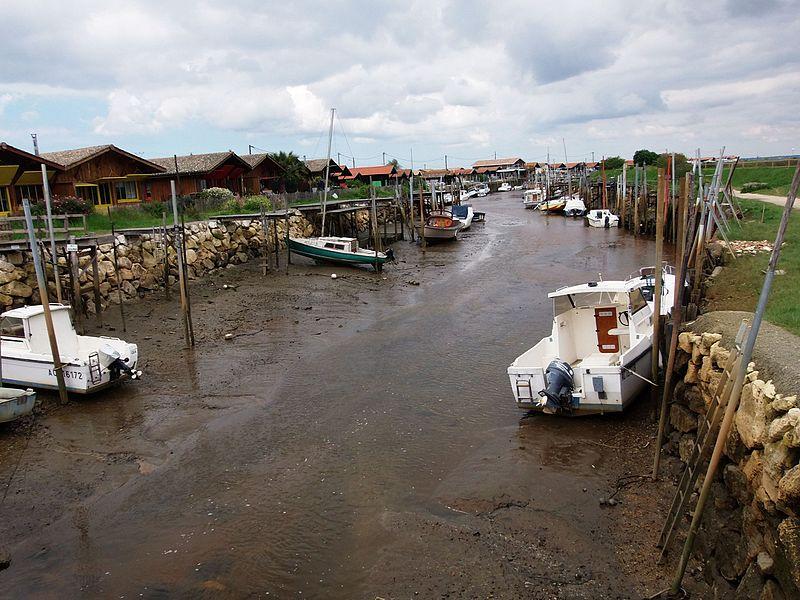 Port de Larros, port ostréicole et de plaisance à Gujan-Mestras (bassin d'Arcachon, Gironde, France) à marée basse, depuis la rue du maréchal Foch. Port avec pinasses ostréicoles, pinassottes, sardinières, etc. Voir aussi autre cliché et port de Meyran.