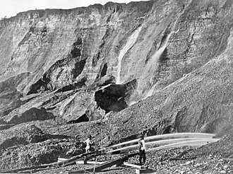 Bear River (Feather River tributary) - Gold miners using hydraulic mining to excavate an eroded bluff with jets of water at Dutch Flat, California, sometime between 1857 and 1870.