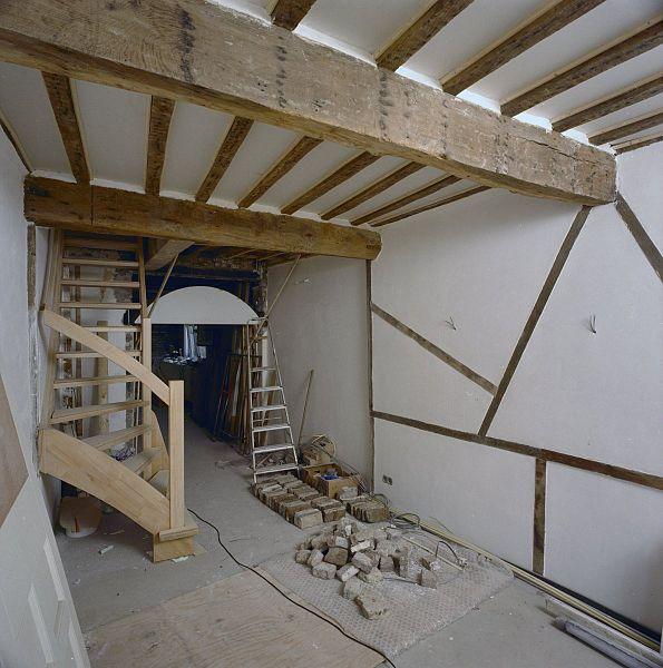 Description Interieur, woonkamer met vakwerkwand en open trap, tijdens ...