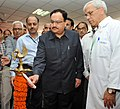 """J.P. Nadda lighting the lamp to inaugurate an exhibition """"Be Clean-Be Healthy"""", on the occasion of 60th Institute Day of AIIMS, in New Delhi. The Director, AIIMS, New Delhi, Prof. M.C. Mishra is also seen.jpg"""