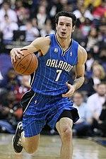 """Un hombre de piel clara es dribla una pelota de baloncesto.  Él está usando un uniforme de baloncesto azul con la palabra """"Orlando"""" en la camiseta."""