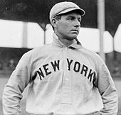 "A waist-up photo of a man in a white baseball uniform reading ""NEW YORK"" across the chest and a white baseball cap. The man is looking to the right of the image."