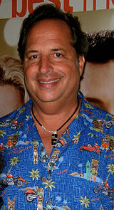 A black-haired man with a blue based shirt and a necklace looks straight at the camera smiling.