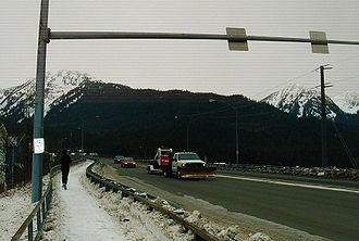 Juneau–Douglas Bridge - A jogger heads west up the bike path toward Douglas Island as traffic approaches mainland Juneau, as seen from the mainland side