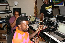 Rapper Kanye West working in a studio