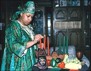Kwanzaa - A woman lighting kinara candles