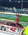 Larson thrusts the checkered flag in the air after winning the 2017 Federate Auto Parts 400.jpg