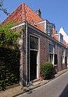 foto van Lage huis met rechte gootlijst, ramen met roedenverdeling en halve luiken