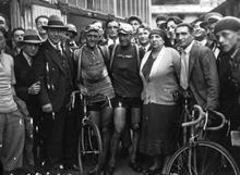 Photographie en noir et blanc montrant des cyclistes à l'arrivée d'une épreuve posant aux côtés de personnes habillées en civil.