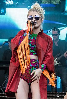 Margaret performing onstage wearing two piece floral bodysuit and fringed red jacket. She also wears sunglasses.
