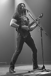A long-haired man playing guitar onstage