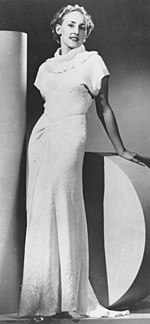 Model posing in a glamorous 1930s evening gown.