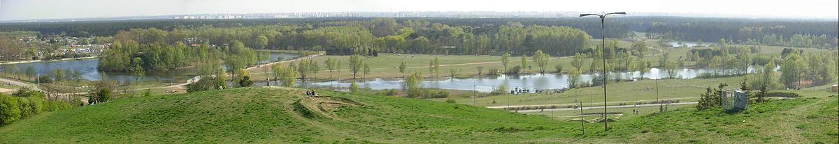 Polski: Fragment Leśnego Parku Kultury i Wypoczynku. Pośrodku staw parkowy o powierzchnu 10 ha i długości 1,5 km. Po lewej ptasia wyspa (1 ha), znana z kilkutysięcznej kolonii lęgowej mewy śmieszki