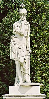A white statue of a man in front of a green hedge. The statue was sculpted in the fashion of the Roman army, wearing the helmet and livery of the army. The statue has one arm raised up to its chin and the other behind it, resting on another piece of the sculpture.