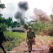 color photograph of a Marine calmly walking away from an exploding hut at the edge of a jungle
