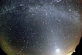 A meteor strikes the bottom left, while the Milky Way arcs overhead and a dawn-like light lines the lower horizon. The image was taken through a curved lens.