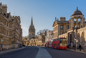 College town - The High Street of Oxford, a prototypical example of a university town. There is no central campus, rather university buildings are scattered around the city between shops, for example those at centre right of the picture.