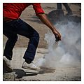 Palestinian Demonstrator picks Tear gas grenade to throw back Kafr Qaddum August 2014 2.jpg