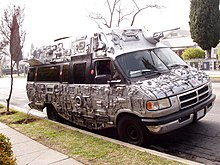 A parked van decorated with electronics and spray painted silver.
