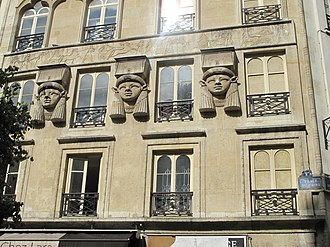 Egyptian Revival architecture - Foire du Caire building (1828), from Paris, the earliest manifestation of Egyptian Revivalism: façade adorned with heads of the Egyptian goddess Hathor
