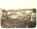 An old photograph showing a crowded square in front of a large, white, multi-storied building