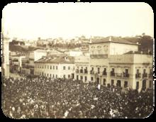 Uma fotografia velha mostrando uma praça lotada na frente de um grande edifício branco, de vários andares