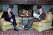 Ronald Reagan and Mikhail Gorbachev sit in plush chairs in front of a stone fireplace