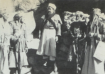 Yemeni Prime Minister, Prince Hassan, talking to tribesmen outside his cave in Wadi Amlah, December 1962 Prince Hassan in Wadi Amlah.jpg